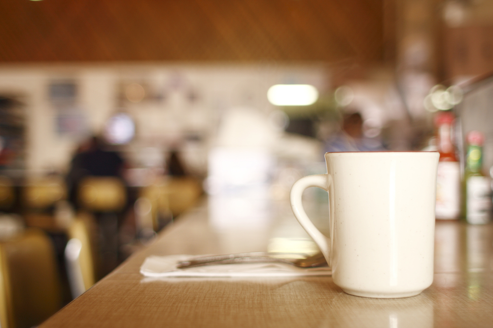 Plain cup of coffee in focus, background of diner out of focus and restaurant serving breakfast in Dallas