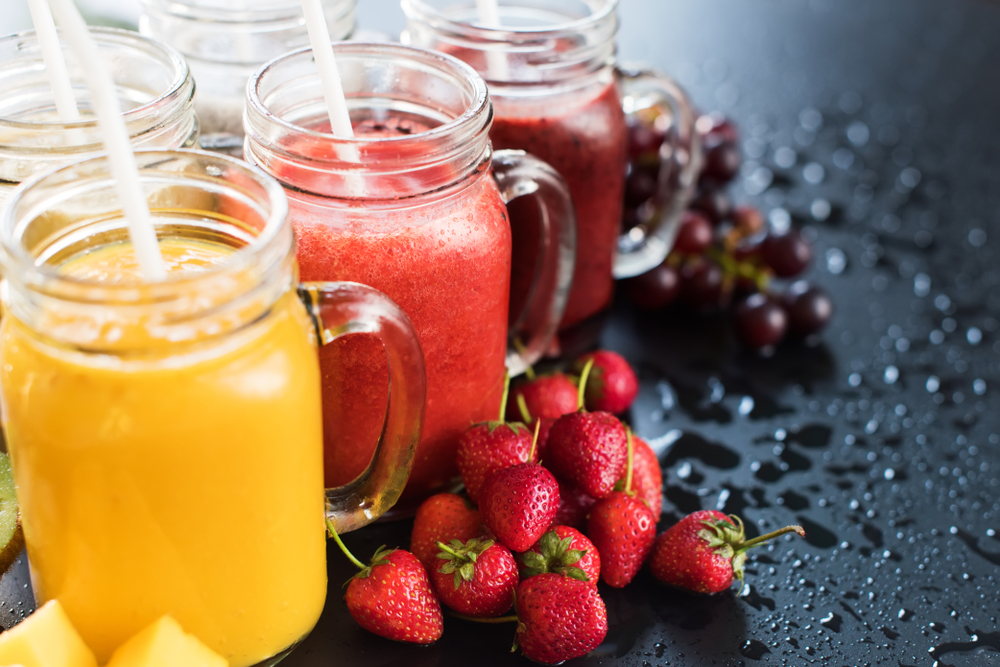 fresh pressed juice in clear jars Orange juice, strawberry juice with fresh strawberries infront, and grape juice with whole grapes