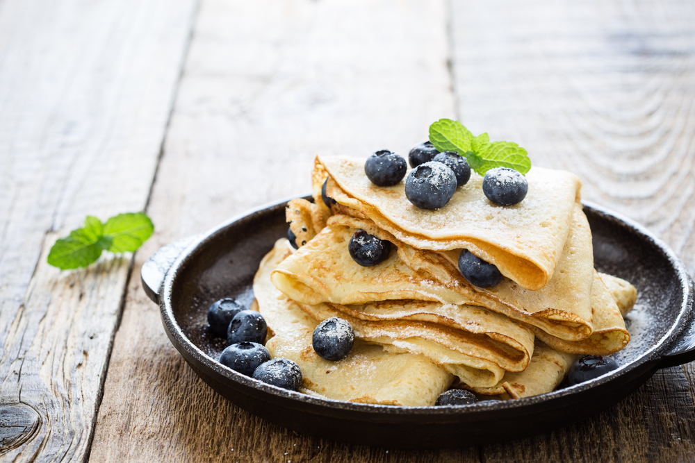 Blueberries on crepes folded like a triangle on a plate served for breakfast in Dallas