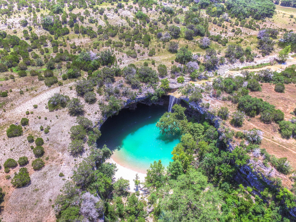aerial view of waterfall flowing into turquoise pool