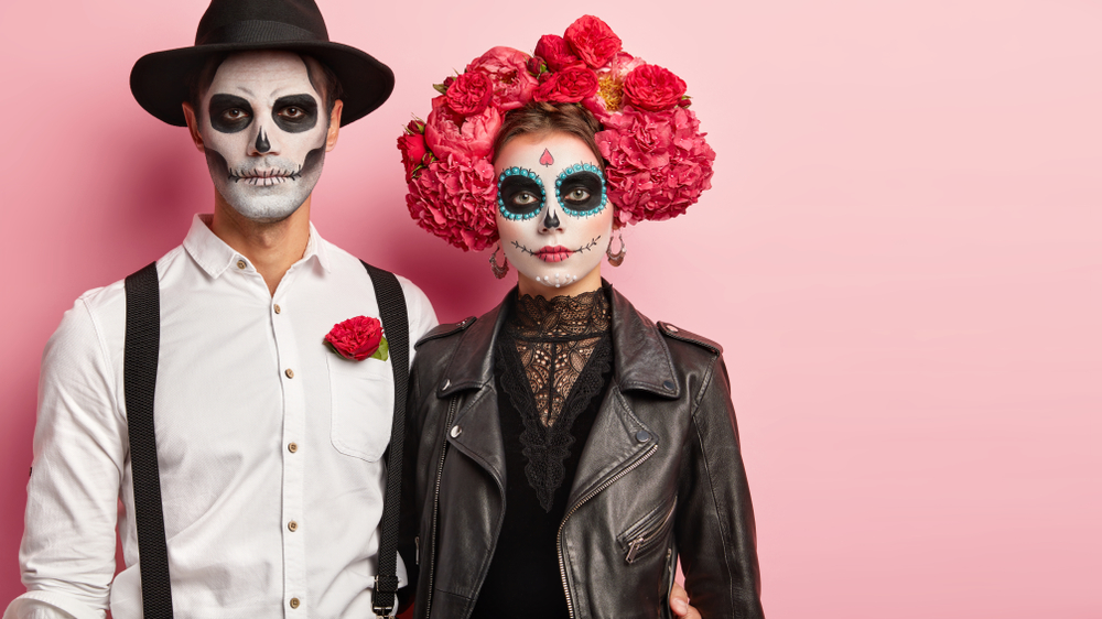 A couple wearing day of the dead skeleton makeup on a pink background