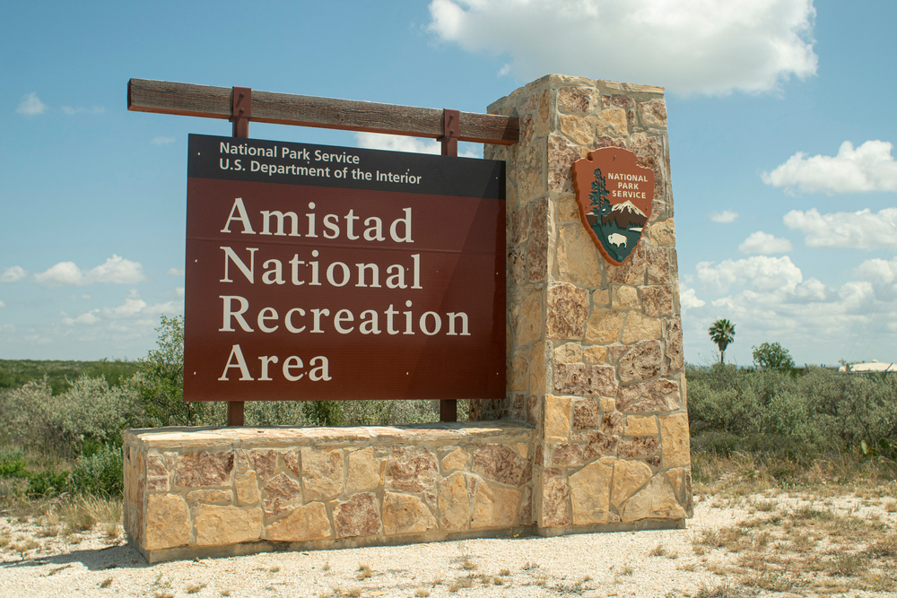 a sign with a stone base that reads Amistad National recreation area on a sunny day
