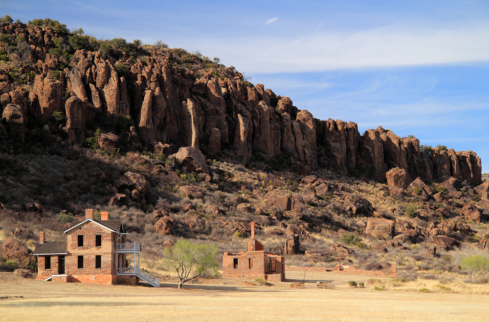 Abandoned brick buildings with rocky mountains in the background on a sunny day