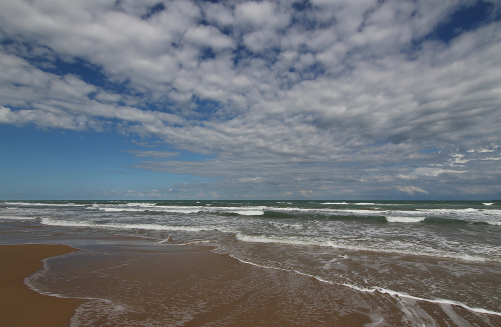 waves crashing onto the shoreline of a beach on a sunny day