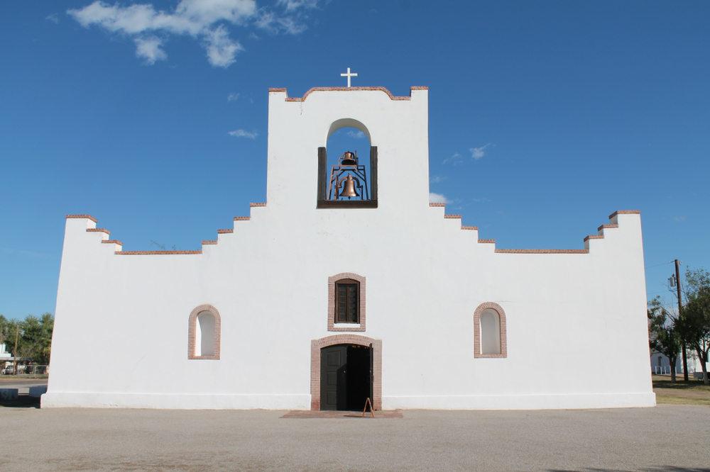 a white geometric shaped building with a bell in the top center on a sunny day