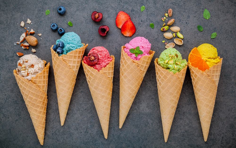 Six different ice cream cones each with a different flavor of ice cream. From left to right, vanilla, blueberry, cherry, strawberry, pistachio, and orange.
