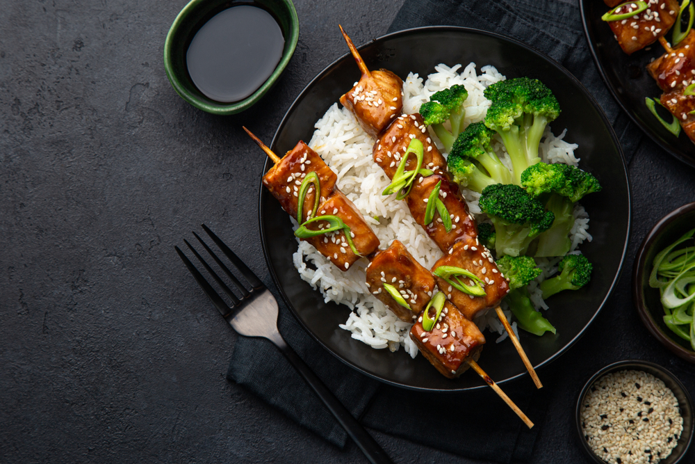 Bowl of white rice with broccoli and tofu skewers.