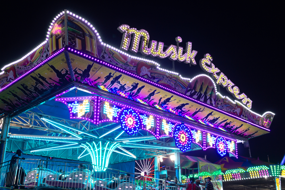 An amusement park ride lit up at night. It has blue, purple, and yellow lights. You can also see cars moving in it. Its one of the best things to do in Lubbock.