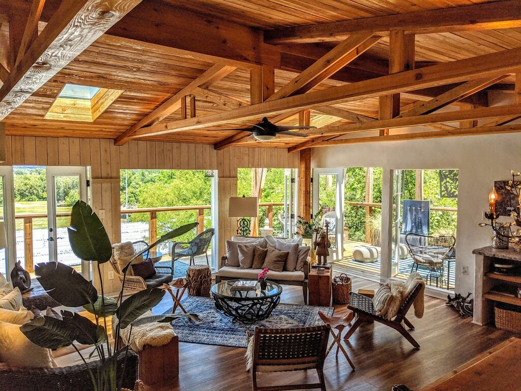 Living room of the Austin Luxury home shows two sets of double doors out onto a spacious deck. The home is furnished in an airy bohemian style. This is one of the best vacation rentals in Texas.
