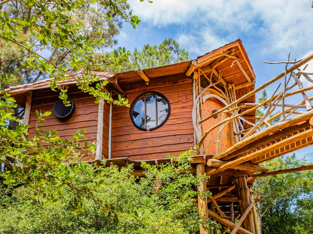 The exterior of the Hobbit's Nest Treehouse. There are round windows and a fantasy themed door knocker. This is definitely one of the best vacation rentals in Texas.
