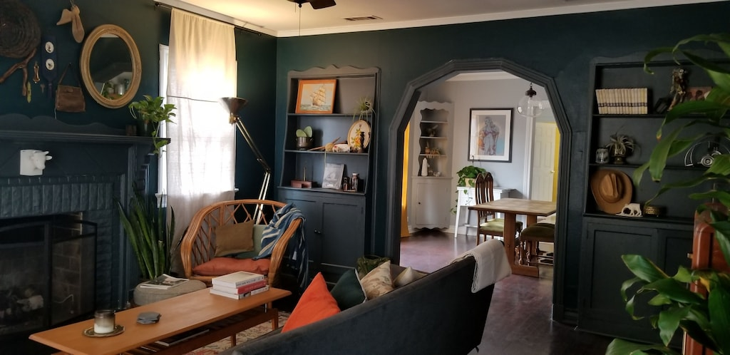 This photo shows the living and formal dining rooms of the Artist Ranchette. The walls are painted a deep salamander green. There are charming built ins full of art and quirky antiques. This is one of the best vacation rentals in Texas.