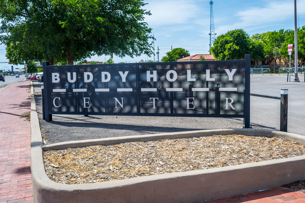 The sign in the parking lot for the Buddy Holly Center, one of the best things to do in Lubbock. It is black, kind of see through, and the words are in white.