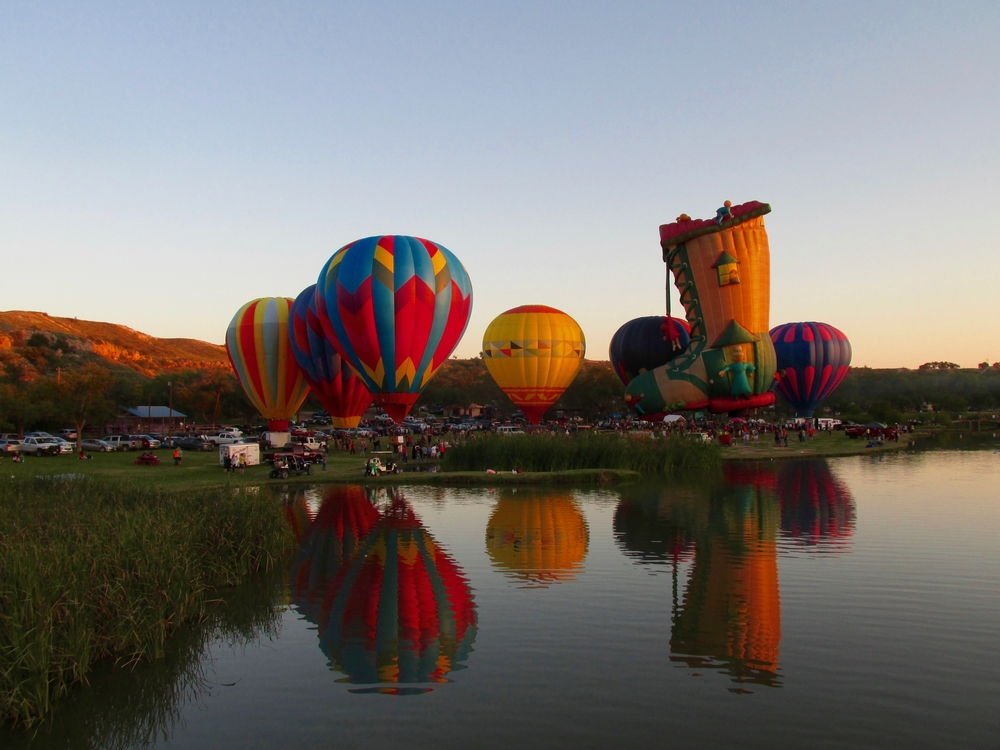 A bunch of hot air balloons on the shore of the Buffalo Springs Lake. The balloons are all different colors and one looks like the 'old lady in the shoe'. You can see a bunch of cars in the grass and it's sunset. One of the best things to do in Lubbock.