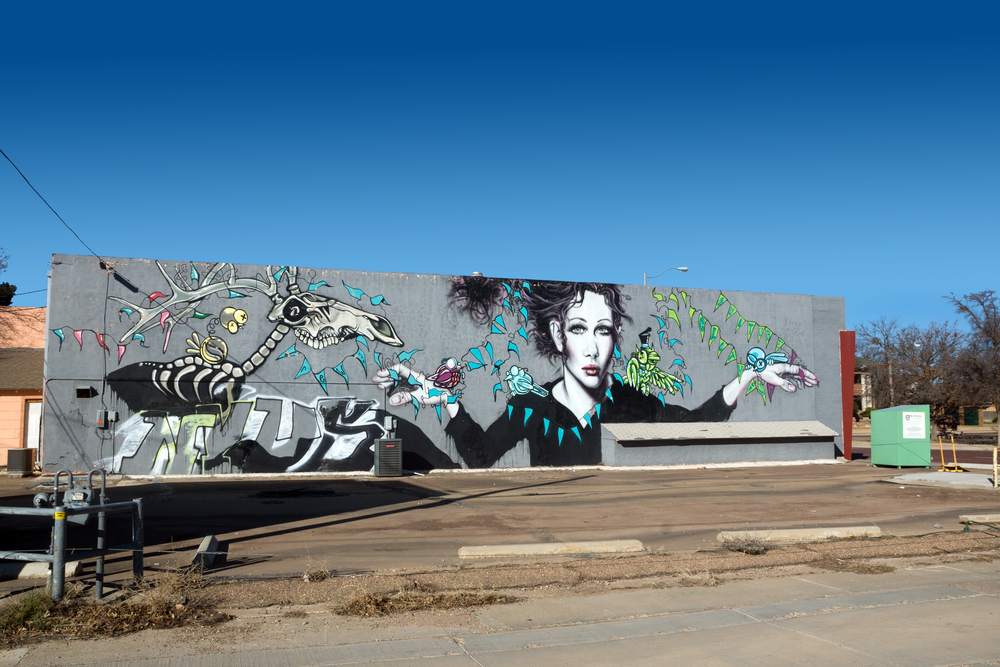 A mural of a woman, a deer skeleton, and vines on the side of a building in Lubbock Texas' historic Depot District.