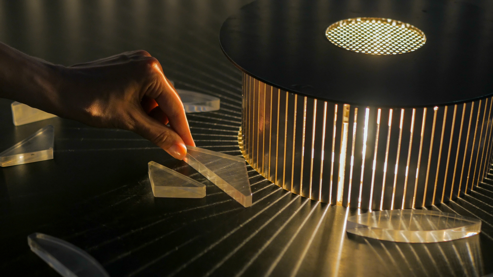A person holding a plastic shape that creates light prisms when placed in front of a light.