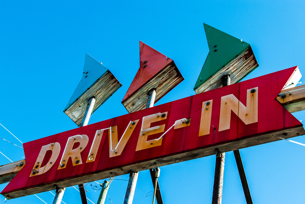 An old neon 'Drive In' sign outside. It is red with the words being white and rusty. Over it are three separate arrows pointing to the right. They are blue, red, and green.