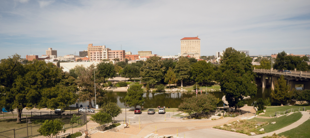 Looking past the river at the small skyline of Lubbock Texas. You can see lots of trees and a few tall buildings.
