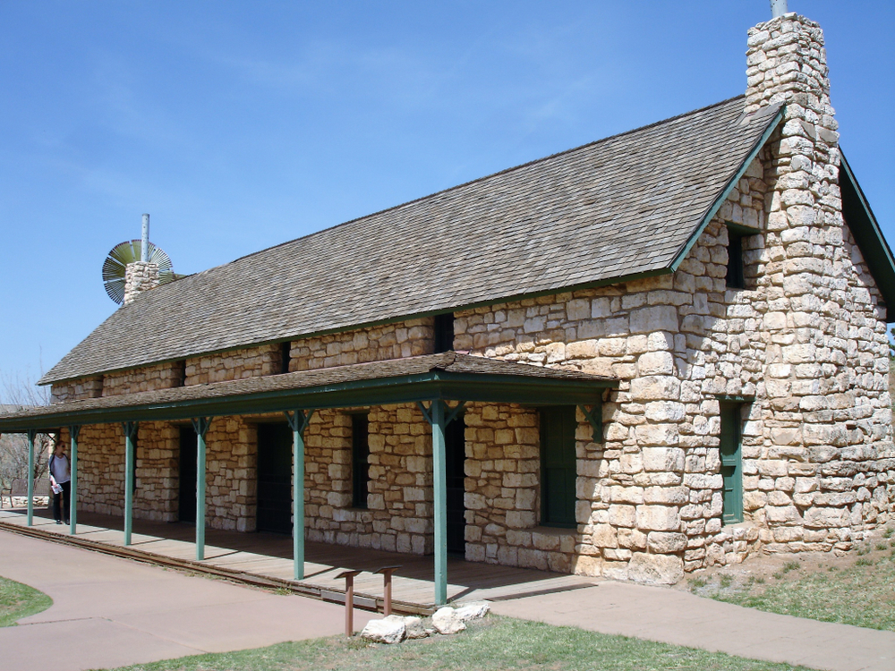 The exterior of an old stone building at the National Ranching Heritage Center. There is a porch with an overhanging off the front of the building and you can see doors and windows in the stone.