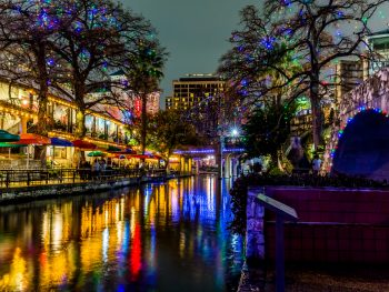 The San Antonio Riverwalk all lit up with multi color Christmas lights at night. The shops are open and lit up and all the lights are reflecting on the river.