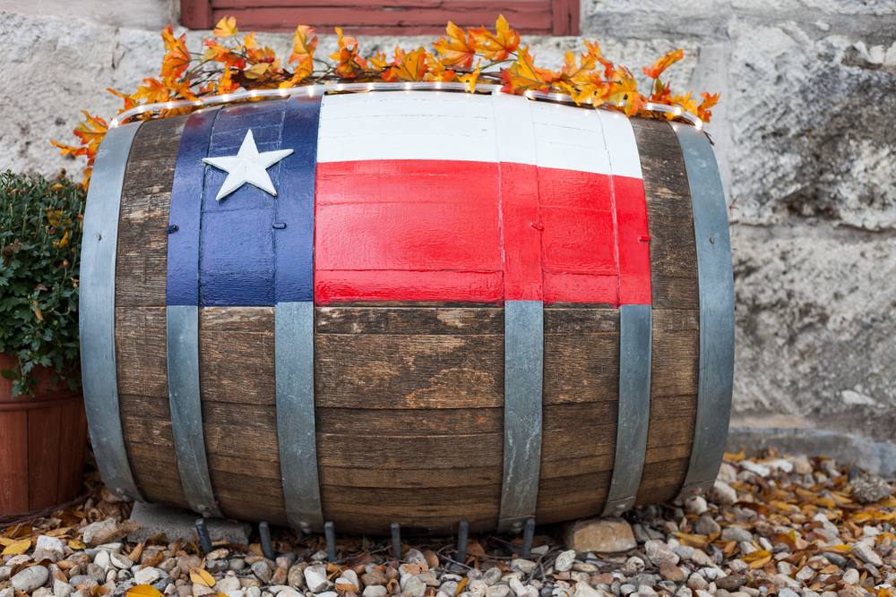 A wine barrel laying on its side next to a stone building. There is a Texas flag painted on the side of the barrel. It has fake fall leaves and twinkle lights rest on top of it. You can find it at wineries, one of the best things to do in Lubbock.