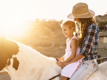 mother and kid riding a horse during sunset