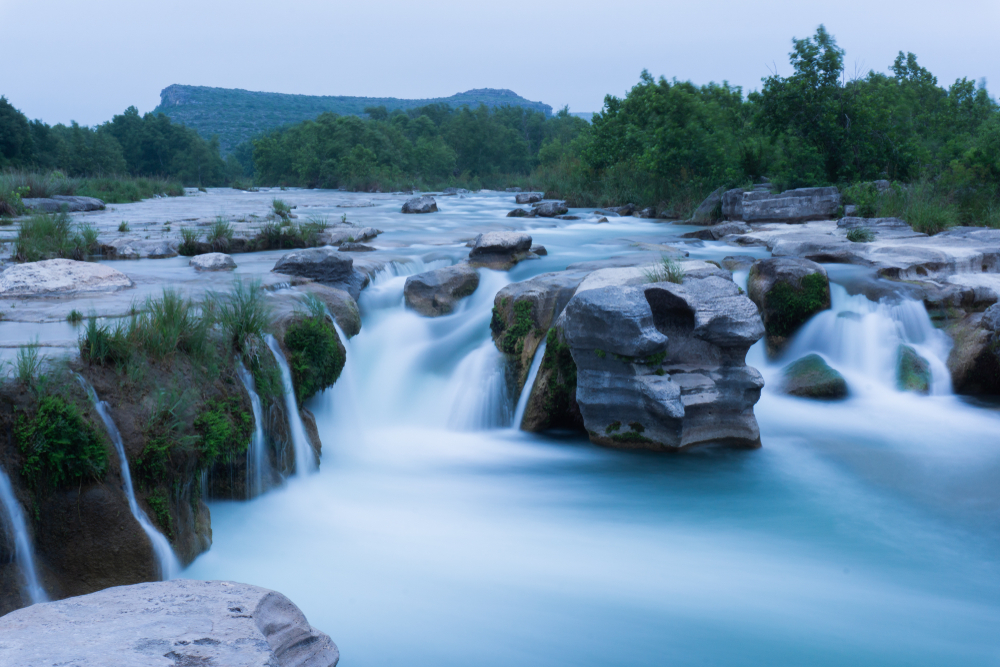 A beautiful waterfall flowing through rocks in a lush green landscape