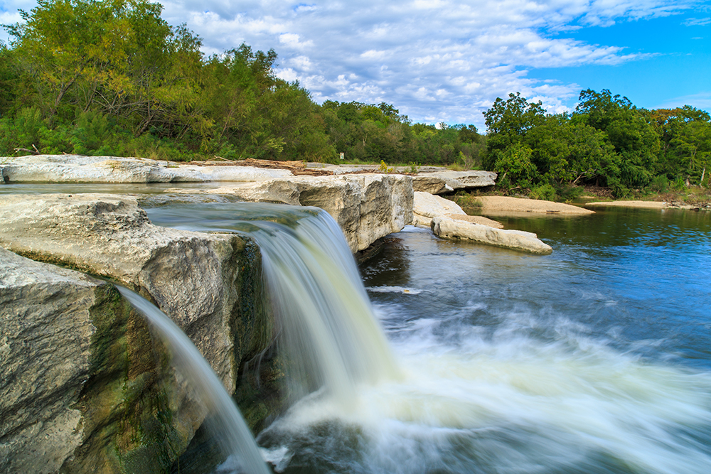McKinney Falls a double waterfall flowing into water below on a sunny day