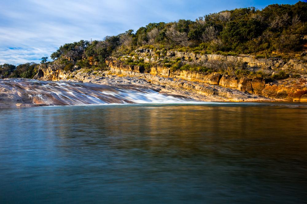 Pedernales Falls flowing over rocks into the Pedernales River at sunset