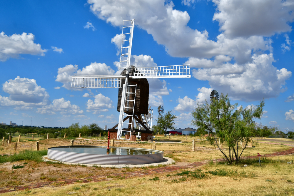 A large dutch looking windmill that is dark brown with white fans in a field in Texas. In front of it there is a small water retention pond. The sky is bright blue with big fluffy clouds.