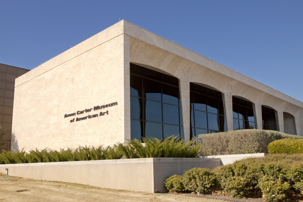 photo of the exterior of the Amon Carter Museum of American Art which is a beige, modern building with square arches and windows covering the front. There are bushes and greenery surrounding the building.