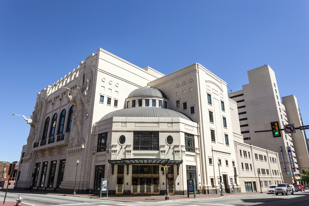 Photo of the exterior of Bass Hall which is white with large angels with trumpets carved into the side and art deco details.