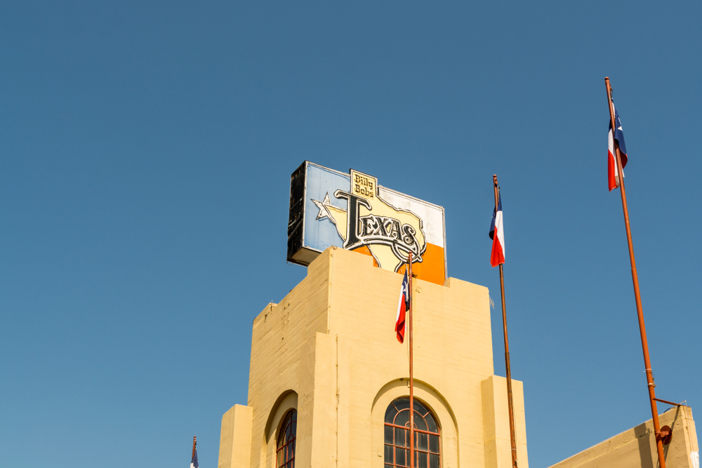 Photo of the top of Billy Bob's Texas with a sign on top of the building in the shape of the Texas Flag and 3 Texas flags displayed outside. Billy Bobs is one of the best things to do in Fort Worth.