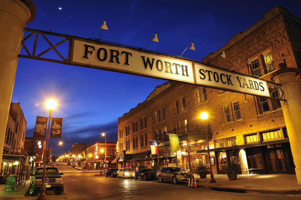 """Photo of the Stockyards at night. The famous """"Fort Worth Stockyards"""" sign stretches across the street lined with historic buildings and cars parked along the street."""