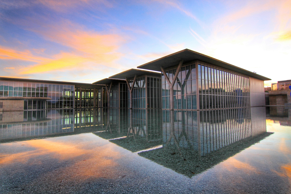 Photo of the Modern Art Museum, a modern complex made up of rectangular buildings covered in glass windows reflecting into a large reflecting pool that surrounds it. The Modern Art Museum is one of the best things to do in Fort Worth.