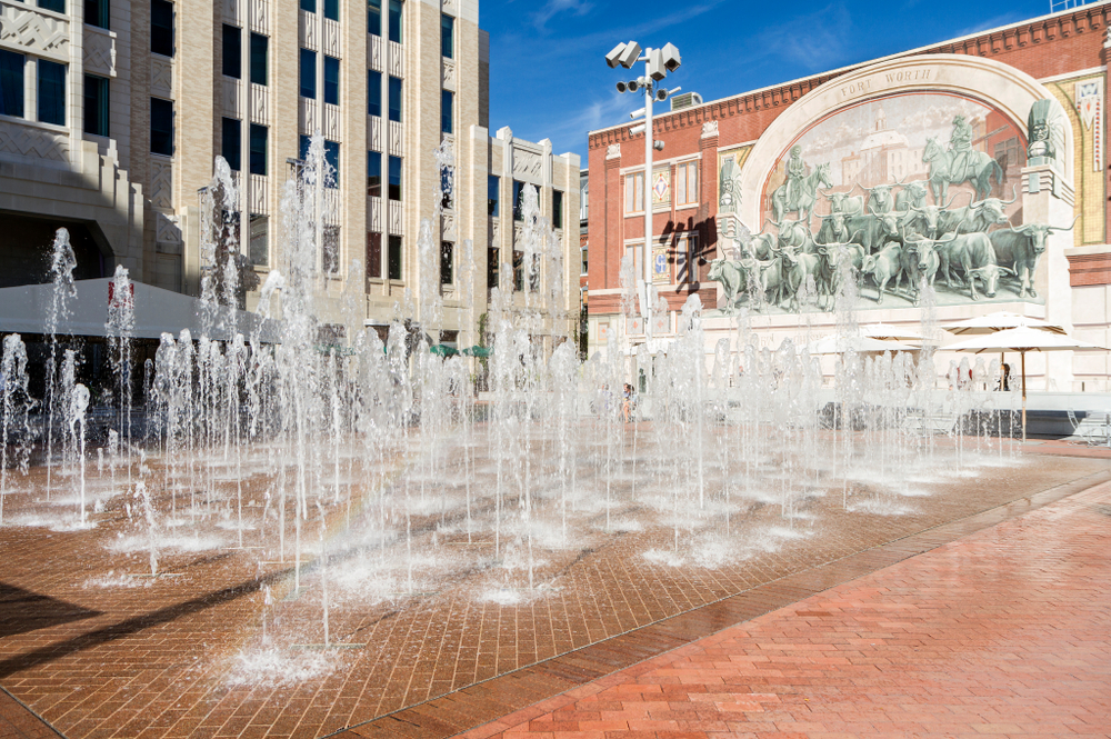 Photo of fountains coming out of the ground surrounded by downtown buildings in Sundance Square. One building has a painting of horses and Texas longhorns.