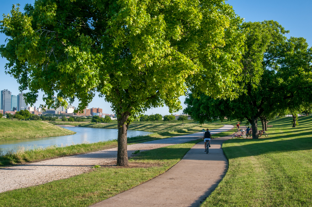 Photo of a person riding a bike down a sidewalk surrounded by tall green trees and grass with trinity river flowing alongside and the Fort Worth Skyline in the background at Trinity Park.