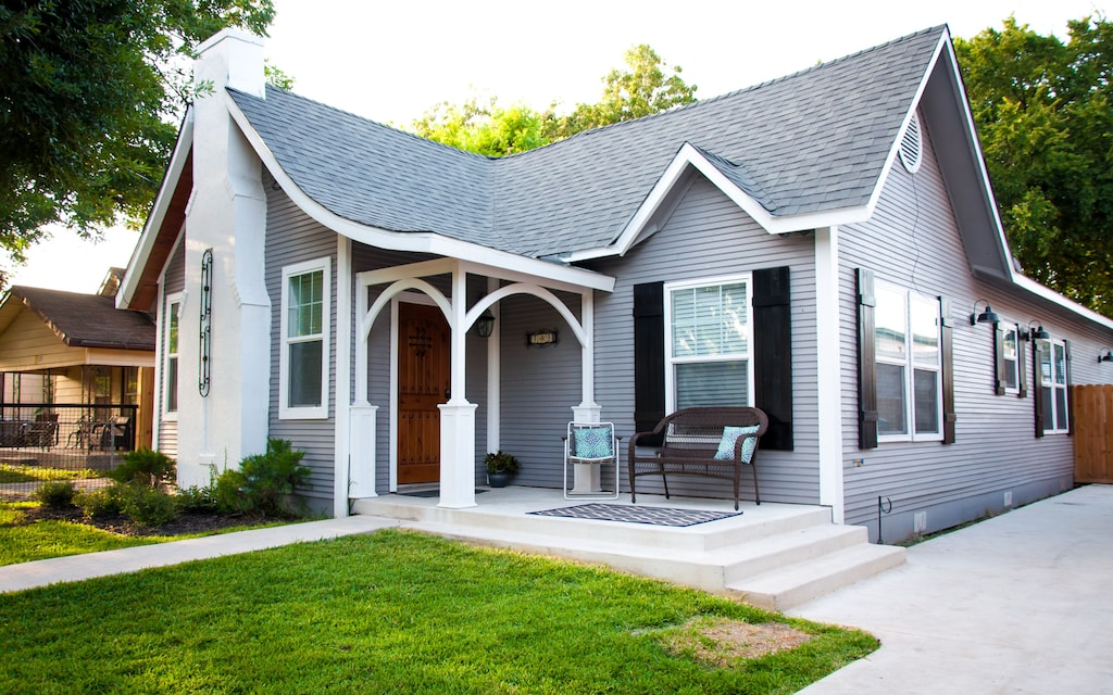 Charming grey house with a large front porch and lots of curb appeal.