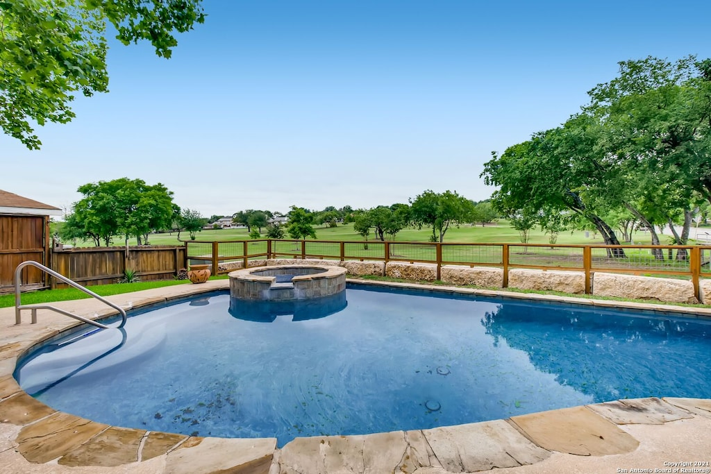 View of the pool and hot tub overlooking the expanse of golf course behind this VRBO.