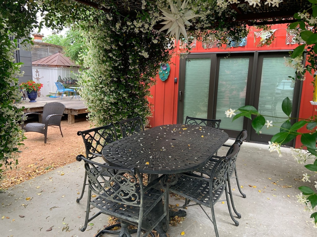 An outdoor table for 6 under a pergola of fragrant jasmine flowers. A cool star shape light is above the table. The red cottage is visible in the background. This is one of the best VRBOs in Texas.