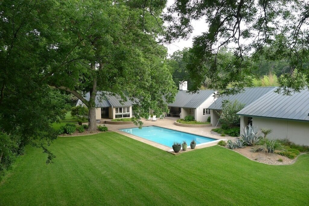 The sweeping lawn and 300 year old pecan tree framing the full sized pool on this property. This is one of the best airbnbs in San Antonio.
