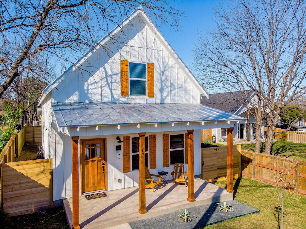 The white exterior with wooden shutters of this Urban Farmhouse. It has a very cute tin roof front porch. This is one of the best Airbnbs in San Antonio.