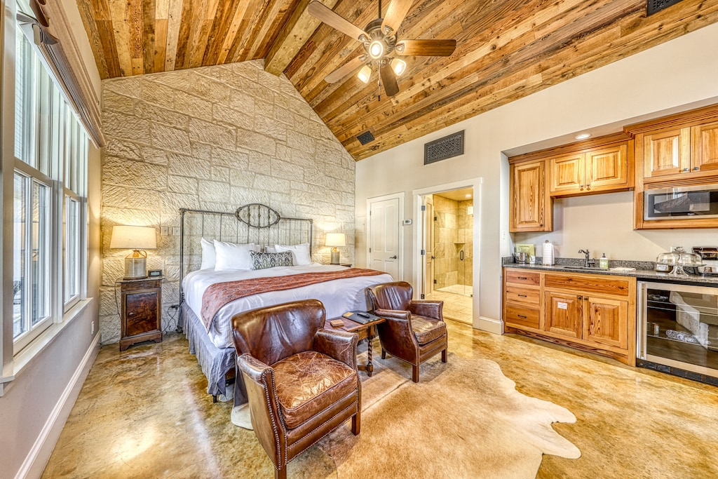 interior of a cabin bedroom with a historic stone wall