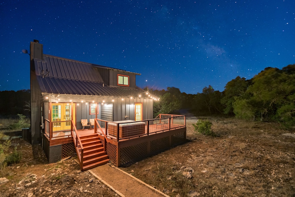 a charming cabin at night with twinkle lights