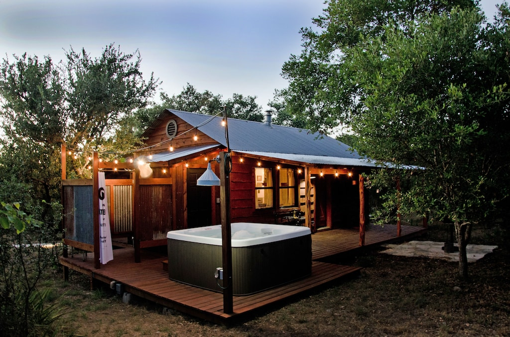 one of the most charming cabins in Texas Hill Country with twinkle lights and a hot tub