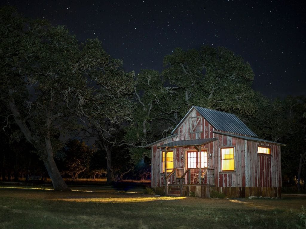 a cabin in Texas Hill Country at night with stars in the sky