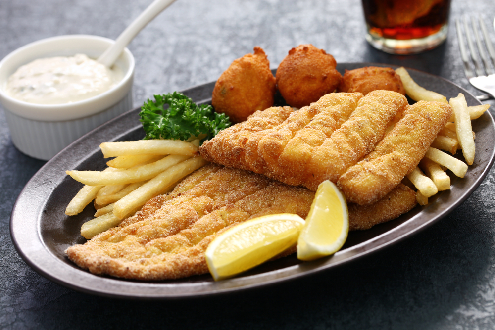 Fried catfish with thin french fries and hush puppies on oval plate