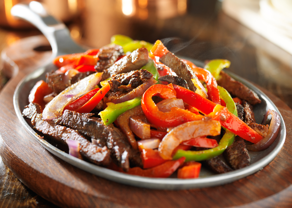 Plate of fajitas with beef strips, onions and red and green peppers with steam coming off of dish at one of the best restaurants in Waco