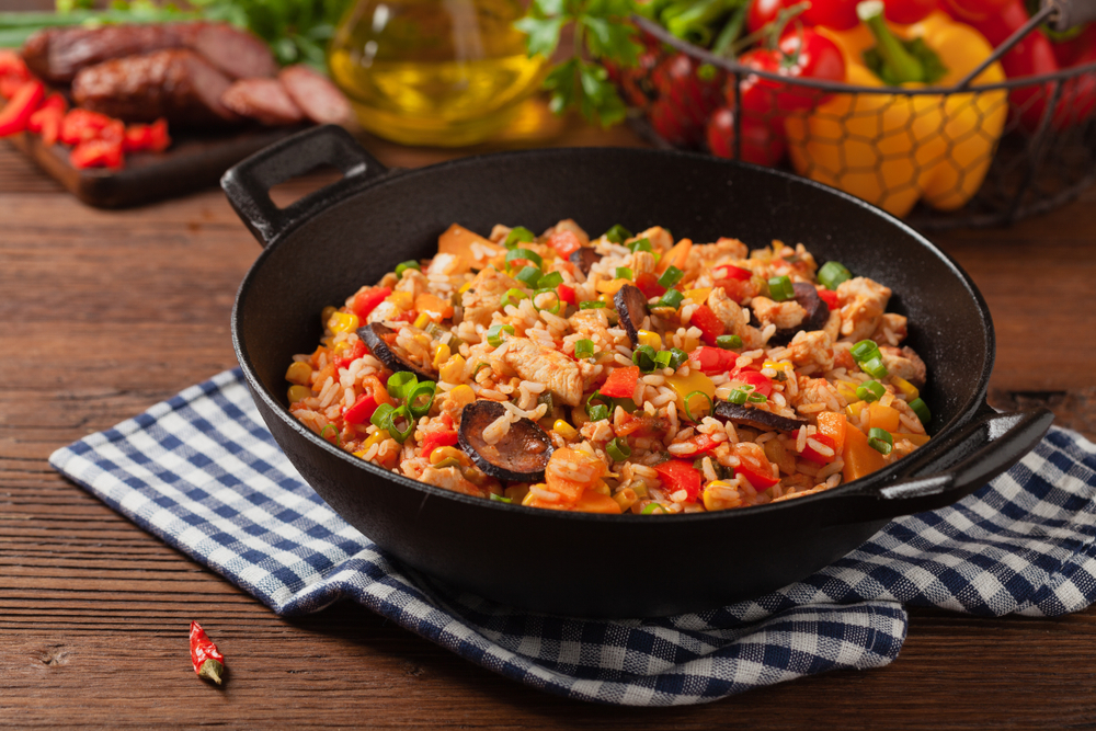 Wok style bowl with Jambalaya, a rice dish with vegetables, meat and seafood.