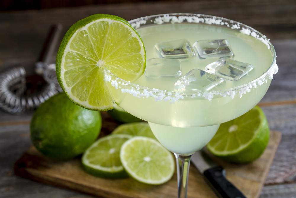 Margarita with ice and a slice of lime on edge of salted rim of glass. Limes on a cutting board in the background.