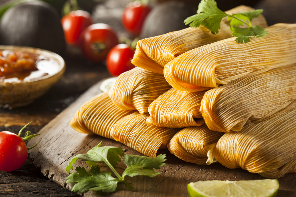Plate of tamales with tomatoes in the background.